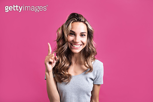 Beautiful smiling woman with index finger up with hair and makeup on a glamorous pink background