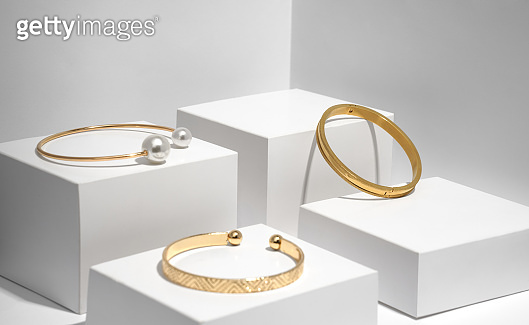 Three modern golden bracelets on white geometric boxes