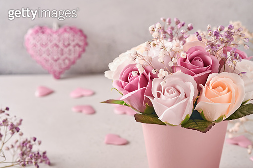 Festive composition with beautiful delicate roses flowers in pink round box on light gray background. Flat lay, copy space.