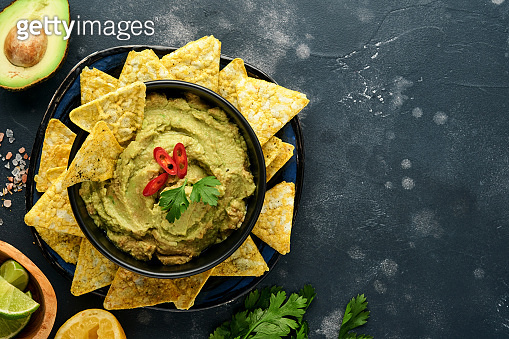 Guacamole. Traditional latinamerican Mexican dip sauce in a black bowl with avocado and ingredients and corn nachos. Avocado spread. Top view. Copyspace