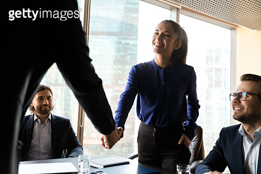 Smiling diverse businesspeople shake hands at meeting