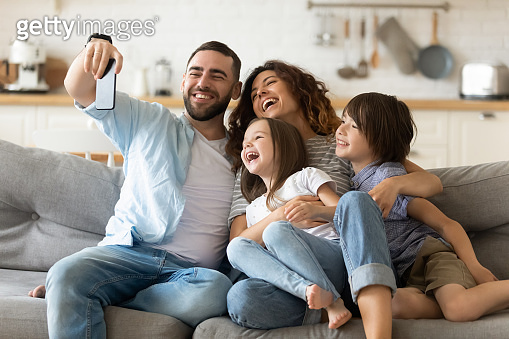 Happy parents with kids having fun, using mobile device