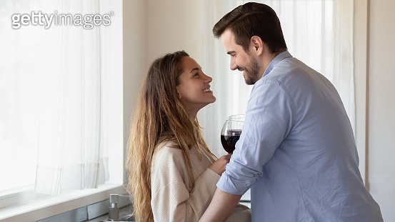Passionate loving couple hugging at kitchen holding glasses of wine