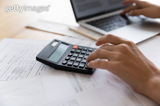 Woman professional bookkeeper at work counting expenses on electronic calculator