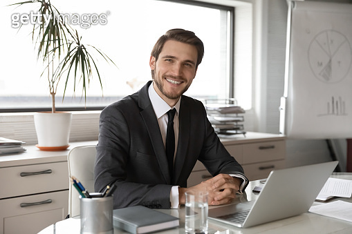 Portrait of smiling businessman posing in own office