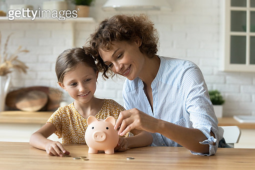 Friendly mom and daughter kid thrift coins in piggybank