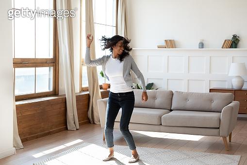 Happy African American woman dance in living room