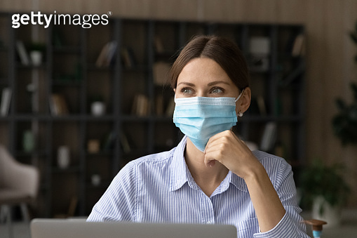 Pensive woman worker in facial mask at workplace