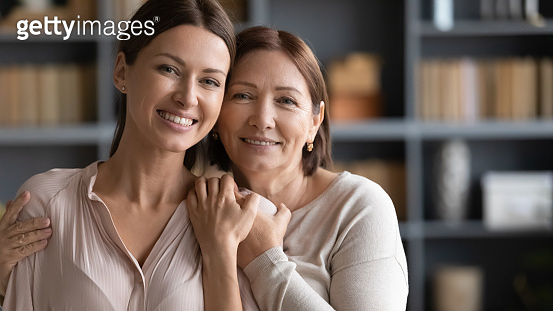 Head shot portrait happy two generations of women hugging