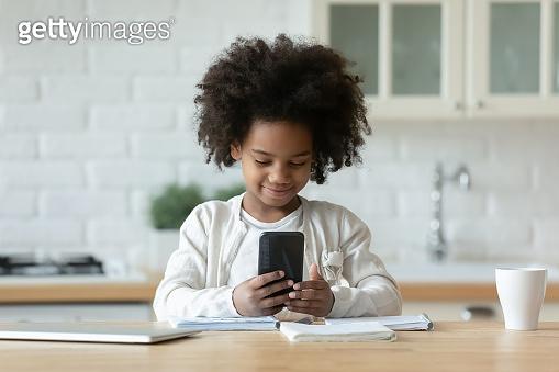 Pretty African American little girl using phone, distracted from studying