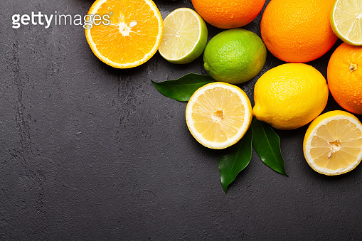 Fresh ripe citrus fruits on stone background