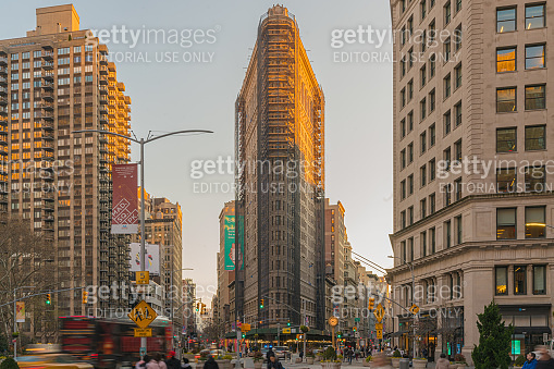 Crowd people tourist and taxi car traffic moving in front of The flatiron famous landmark in Newyork United states sunset moment