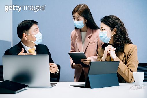 Asian Business people wearing protective face masks at work during COVID-19 pandemic.