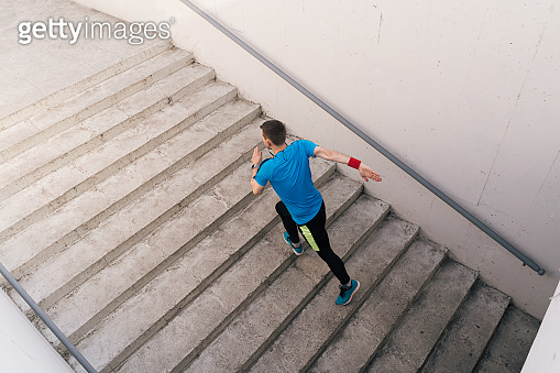 Young man practicing interval workout on stairs