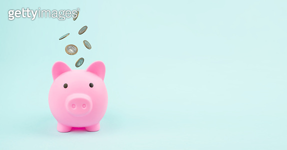 Pink Piggy Bank with Falling Coins, concept of savings. Financial savings and banking economy