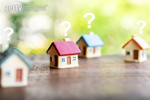 miniature house model with question mark, looking for new home, buy or rent real estate concept