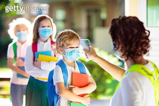 Temperature check at school. Child in mask.