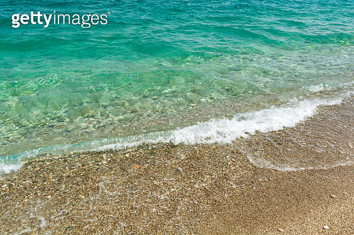 Soft turquoise sea wave on pebble beach. Nature background