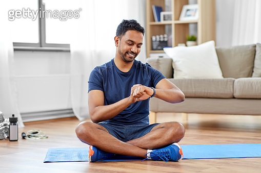 smiling indian man with fitness tracker at home