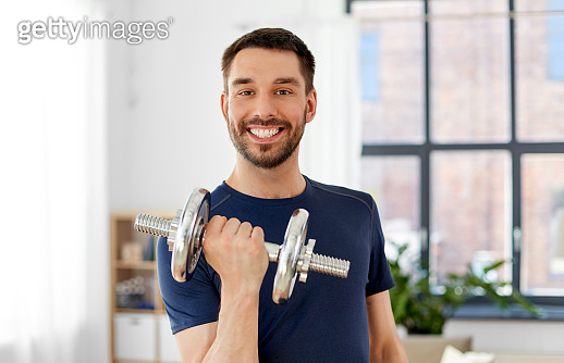 happy smiling man exercising with dumbbell at home