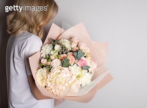 Woman holding large bouquet of hydrangeas, roses