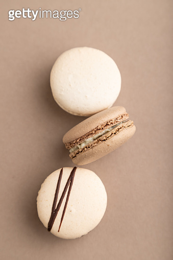 Brown and white macaroons on beige pastel background. top view, flat lay, close up, still life. Breakfast, morning, concept.