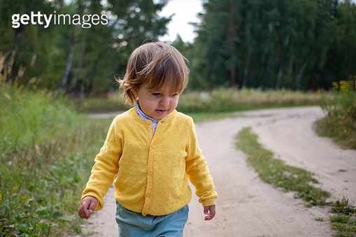 Toddler walking alone on desolate country road. rural country sand road on ranch or farm in forest