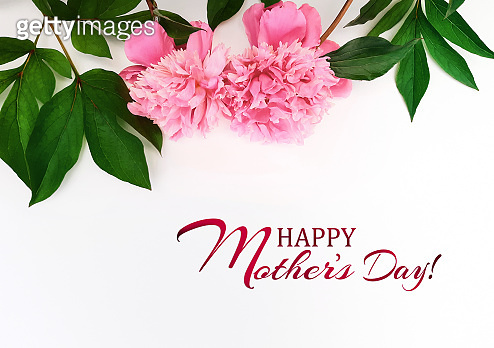 Composition of pink peonies, leaves on a white background. Fresh flowers. Inscription Happy Mother's Day. Advertising banner, poster for Mother's Day. Flat lay, top view, close up, copy space