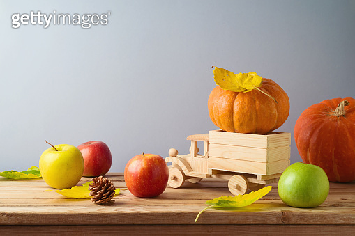 Thanksgiving holiday and autumn season concept with pumpkin, apples and fall leaves in toy truck on wooden table