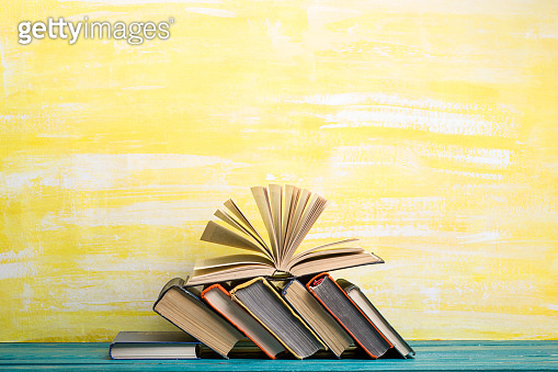 Books on bookshelf in Library. Back to School education concept on colored abstract yellow background. Open hardback book stack in a raw on wooden desk table.