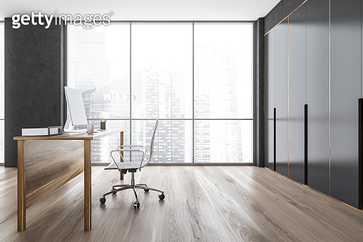Wooden and grey office cabinet with table and computer on parquet floor