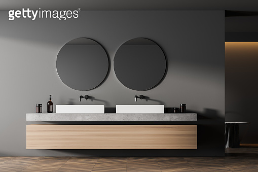 Modern bathroom interior with double sink in eco minimalist style with brown wooden parquet floor. And two round mirrors. No people. 3D Rendering