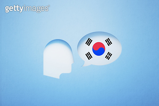 Korean Learning And Speaking Concept - Speech Bubble Shape Textured With South Korean Flag Sitting Next To A Cut Out Human Head On Blue Background