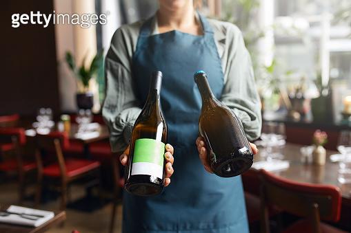 Waitress holding wine bottles