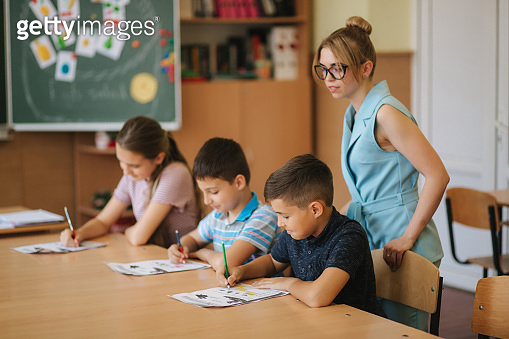 Teacher helping school kids writing test in classroom. education, elementary school, learning and people concept. Two boys and one girl stay after school