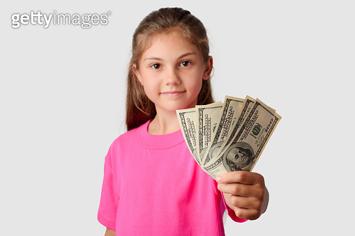 Smiling little girl giving a pack of money to a camera.
