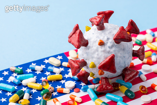Coronavirus model on flag of the USA with many pills and capsules