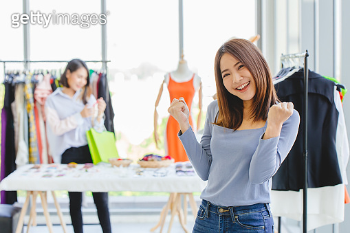 Young Asian girl teen SME clothing shop owner happy smile gladful with opening new business promotion and customer.