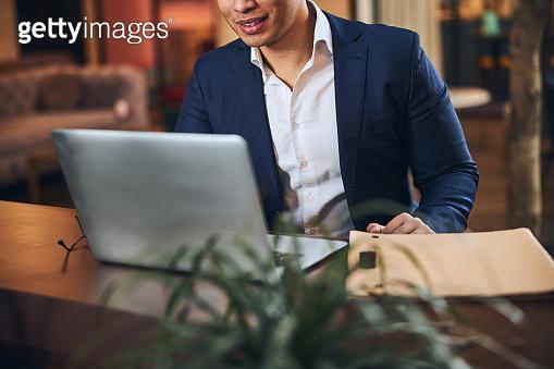 Elegant remote worker sitting before his computer