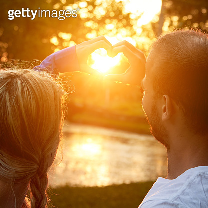 Young adult couple holding heart - shape symbol for love outdoors.