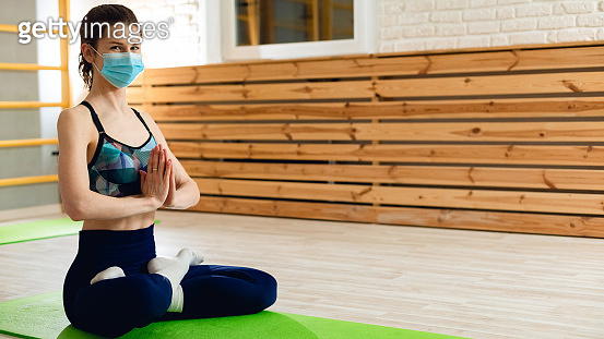 Young beautiful woman is training for health care. Portrait with protective face mask. Lockdown concept, training at home. Aerobics photography, person is sitting on exercise mat