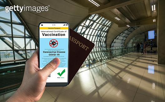 Traveler holds vaccine passport certificate to show COVID 19 vaccination status
