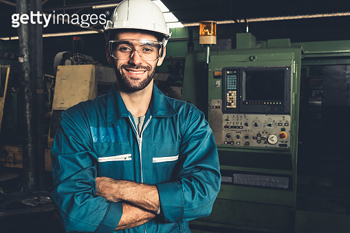 Young skillful factory worker or engineer close up portrait in factory