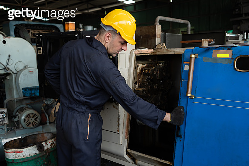 Skillful factory engineer or worker do machine job in manufacturing workshop