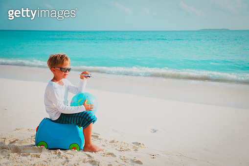 travel to beach-little boy with toy plane, globe and luggage at sea