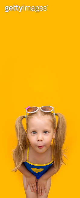 Naughty blonde girl in a blue swimsuit leaned into the camera in surprise. Little girl with ponytails and sunglasses on her head on a yellow background. Vertical banner with place for text. Copyspace.
