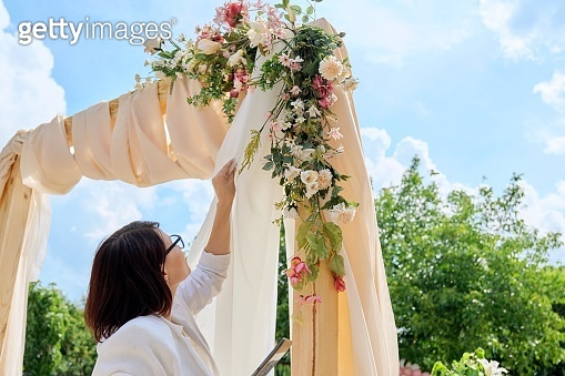 Decorating arch with textiles with flowers and plants. Woman organizer, owner, with digital tablet near wedding arch