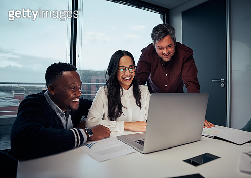 Happy multiethnic group of business people looking at laptop discussing new project in office
