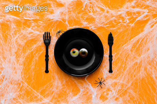 Scary halloween dinner party concept with jelly eyeballs on black plate