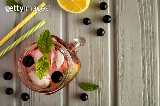 Cold lemonade with  black currant, lemon and mint on the gray wooden background. Top view.